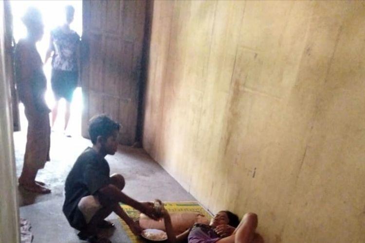 SLF menyuapi ibunya SA yang mengalami sakit gangguan jiwa, di rumahnya Demak, Jawa Tengah, Minggu (19/04/2020). Sementara ayahnya dipasung. SLF awalnya berjualan buah ikit tetangganya di Jakarta, tapi harus pulang karena corona. Ia kini jadi kuli bangunan.