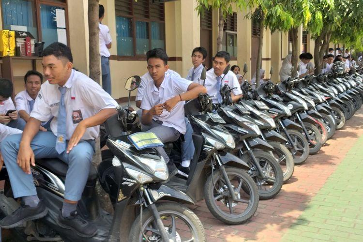 Sejumlah siswa SMA Negeri 4 Tangerang Selatan berkumpul dekat barisan motor yang telah dirapikan oleh satpam sekolah itu, Slamet Gunaedi, Senin (4/2/2019). Satpam tersebut merapikan motor para siswa berdasarkan merek dan warnanya.