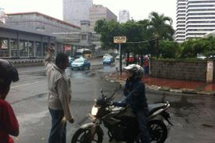Pengendara motor diberhentikan karena hendak melintas Jalan MH Thamrin, Jumat (26/12/2014).