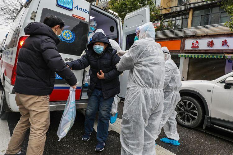 Petugas medis yang mengenakan pakaian pelindung membantu pasien turun dari ambulans di luar rumah sakit di Wuhan, Hubei, China, pada 26 Januari 2020. Penyebaran virus corona sejak Desember 2019 sudah membunuh lebih dari 300 orang di China.