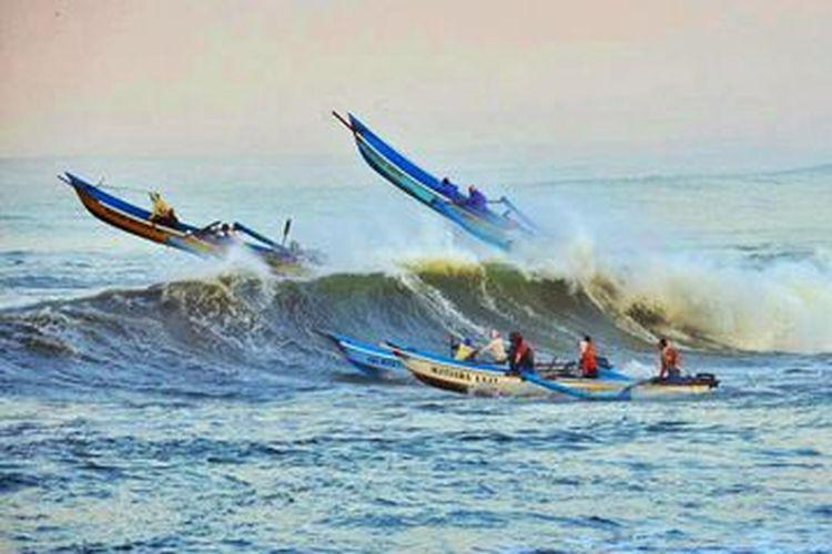 Perahu nelayan menerjang gelombang tinggi di perairan Teluk Penyu, Cilacap, Jawa Tengah.