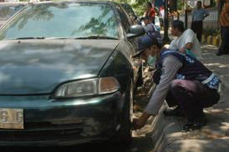 Petugas menggembosi ban mobil parkir sembarangan di Surabaya.