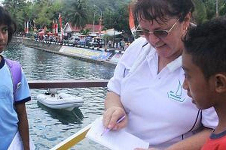 Seorang turis asal Australia dimintai tanda tangan oleh pelajar di Desa Amahusu, Kecamatan Nusaniwe, Kota Ambon, Maluku, Jumat (11/9/2015). Turis tersebut adalah peserta Darwin-Ambon Yacht Race and Rally 2015.