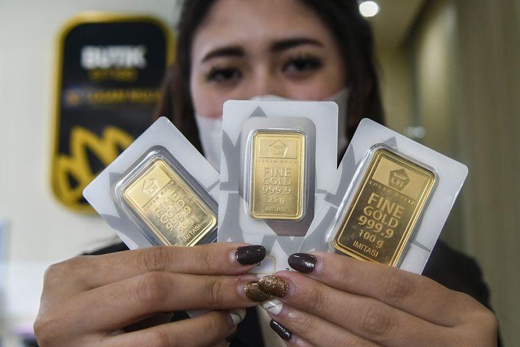 Karyawan menunjukan emas batangan di Butik Emas Antam, Kebon Sirih, Jakarta, Senin (18/1/2021).