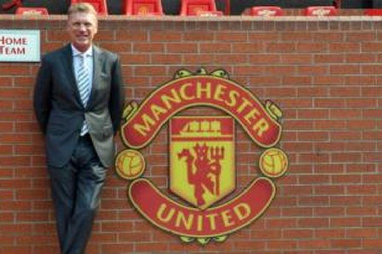 Pelatih baru Manchester United, David Moyes, berdiri di dekat lambang klub. Lambang ini diubah pada 1998 dengan menghilangkan frase