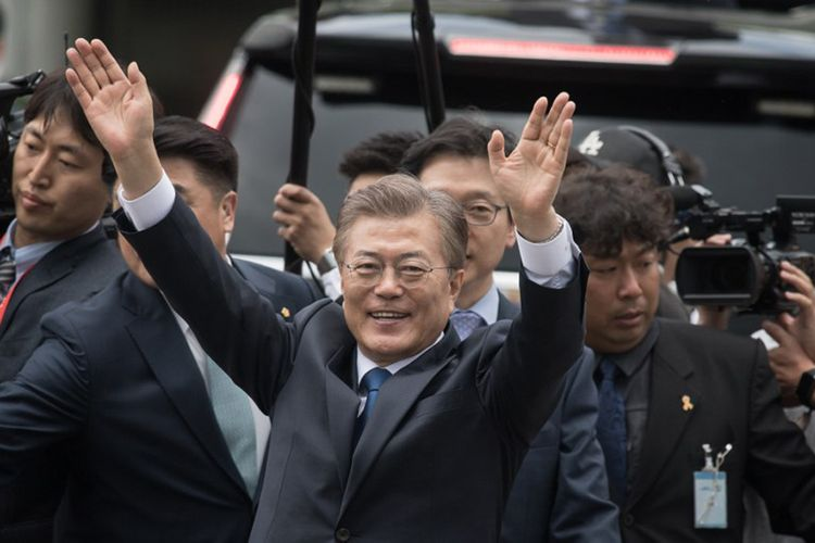 Presiden baru Korea Selatan Moon Jae-In melambaikan tangan ke arah para pendukungnya, saat tiba di Istana Presiden Blue House di Seoul, Rabu (10/5/2017).