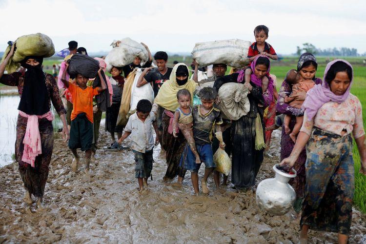 Sekelompok pengungsi Rohingya berjalan di jalan berlumpur setelah melewati perbatasan Bangladesh-Myanmar di Teknaf, Bangladesh, Jumat (1/9).