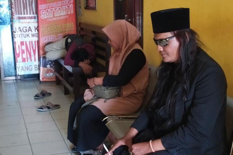 Robi Anjal (38) asal Pontianak, Kalimantan Barat, bersama istri dan anaknya saat menunggu panggilan pemeriksaan polisi di Polres Sampang, Senin (29/7/2019).  Robi adalah pelaku kasus orang mati hidup lagi di Sampang, Madura.