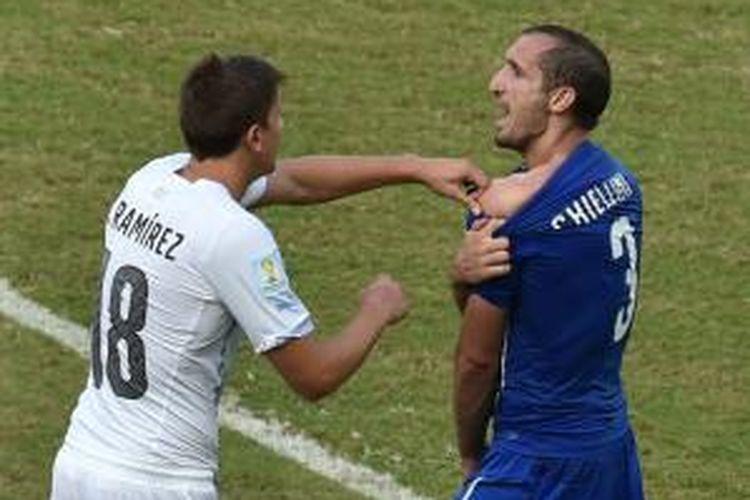 Bek Italia, Giorgio Chiellini, saat berupaya memerlihatkan bekas gigitan striker Uruguay, Luis Suarez, di sela-sela pertandingan terakhir Grup D Piala Dunia 2014 di Estadio Das Dunas, Selasa (24/6/2014).