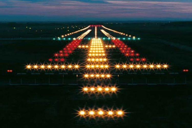 Tangkapan layar pemandangan runway di malam hari yang terangi oleh lampu berwarna-warni.