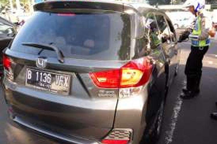 Petugas kepolisian saat menegur pengendara mobil yang berpelat nomor genap di lampu merah Bundaran Senayan pada Senin (27/6/2016). Hari ini merupakan masa uji coba penerapan ganjil genap disejumpah ruas jalan di Jakarta.