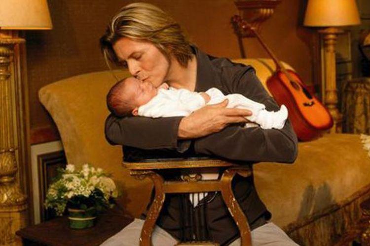 David Bowie menggendong Alexandria Zahra Jones saat masih bayi.