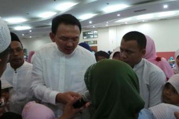 Plt Gubernur DKI Jakarta Basuki Tjahaja Purnama saat bertemu dengan Rumina, janda atlet tunanetra. Basuki berjanji akan mengkuliahkan anak-anak Rumina.