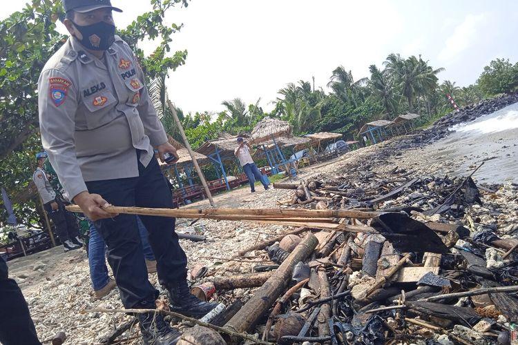 Petugas kepolisian menunjukkan sampah plastik yang penuh limbah. Material yang mirip minyak dan aspal itu mencemari kawasan Pantai Sebalang di Lampung.