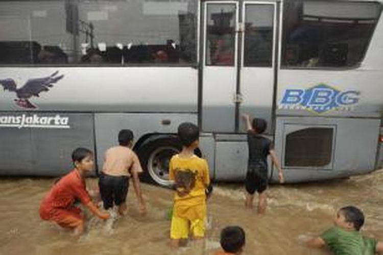Anak-anak bermain di tengah banjir yang menggenangi Jalan Otista, Bidara Cina, Jakarta, Senin (13/1/2014). Hujan yang melanda Jakarta sejak Minggu pagi ditambah meluapnya sungai Ciliwung akibat banjir kiriman dari Bogor mengakibatkan sejumlah kawasan ini terendam banjir sejak Minggu malam. KOMPAS IMAGES/RODERICK ADRIAN MOZES