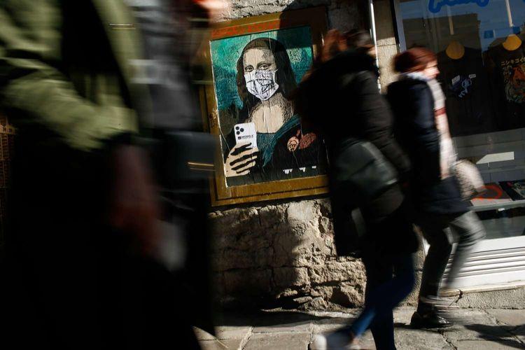 Warga melintas di depan poster karya seniman Italia Salvatore Benintende, yang menunjukkan Mona Lisa mengenakan masker pelindung dan menggenggam handphone bertuliskan Mobil World Virus, di Barcelona, 18 Februari 2020, sepekan setelah Mobile World Congress dibatalkan.