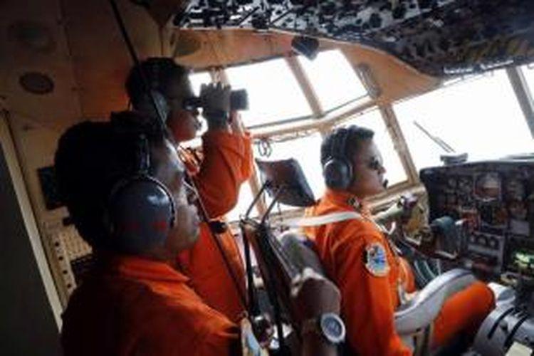 Anggota TNI AU di dalam pesawat C-130 yang terbang dalam operasi pencarian pesawat AirAsia QZ8501 di Selat Karimata, Senin (29/12/2014). Pesawat AirAsia QZ8501 yang mengangkut 155 penumpang serta 7 awak, hilang kontak pada Minggu pagi, saat penerbangan dari Surabaya menuju Singapura.