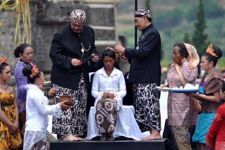 Prosesi pemotongan rambut gembel di pada rangkaian DIeng Culture Festival (DCF)  di Komplek Candi Arjuna, Dieng Kulon, Batur, Banjarnegara.