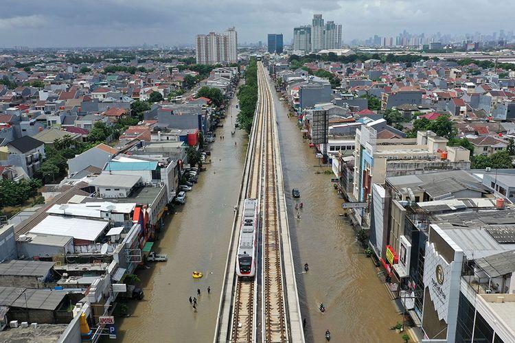 Kereta LRT melintas saat banjir merendam Jalan Boulevard Raya, Kelapa Gading, Jakarta Utara, Minggu (23/2/2020). Hujan deras sejak Minggu, 23 Februari dini hari membuat sejumlah daerah di Ibu Kota tergenang banjir.