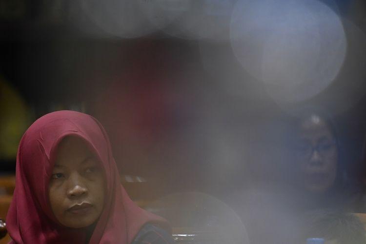 Terpidana kasus pelanggaran Undang-Undang Transaksi dan Informasi Elektronik (UU ITE), Baiq Nuril Maknun  menyimak rapat pleno Komisi III DPR terkait surat persetujuan amnesti di Kompleks Parlemen Senayan, Jakarta, Selasa (23/7/2019). Rapat pleno tersebut untuk meminta tanggapan dari para fraksi terkait surat permohonan pertimbangan amnesti untuk Baiq Nuril dari Presiden Joko Widodo. ANTARA FOTO/Puspa Perwitasari/aww.