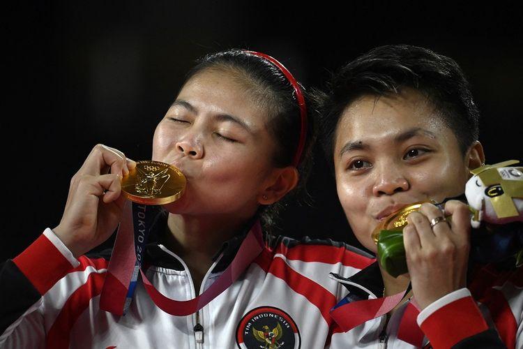 Pasangan ganda putri Indonesia Greysia Polii dan Apriyani Rahayu (kanan) berpose dengan medali emas bulu tangkis ganda putri pada upacara Olimpiade Tokyo 2020 di Musashino Forest Sports Plaza di Tokyo pada 2 Agustus 2021.