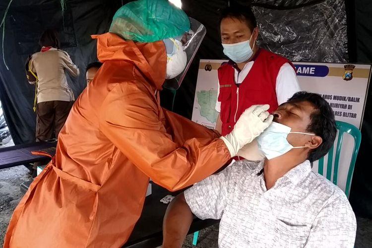 Petugas medis mengambil spesimen swab dari seorang warga yang melintas di pos penyekatan yang dikendalikan Polres Blitar dan Malang di Karangkates, Kecamatan Sumberpucung, Kabupaten Malang, Minggu (16/5/2021)