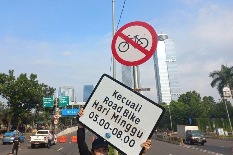 Seorang pesepeda mengangkat papan keterangan rambu uji coba road bike di Jalan Layang Non Tol (JLNT) Casablanca, Jakarta Selatan, Minggu (13/6/2021).