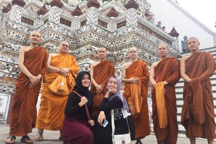 Dinar dan temannya yang berfoto dengan biksu saat berlibur di Thailand.