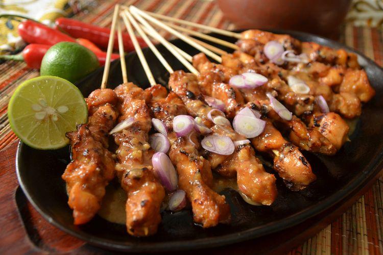 Ilustrasi sate ayam madura siram bumbu kacang, irisan bawang merah, dan jeruk nipis.