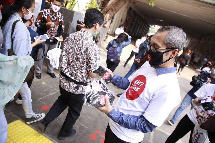 Wakil Ketua KPK Alexander Marwata membagikan masker bertuliskan Antivirus Korupsi di sekitar Stasiun Sudirman, Jakarta, Jumat (26/6/2020).