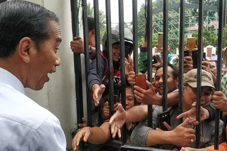 Presiden Joko Widodo (Jokowi) bersalaman dengan warga yang menunggunya di luar pagar GOR Pasar Minggu, Jakarta Selatan, Jumat (22/2/2019).