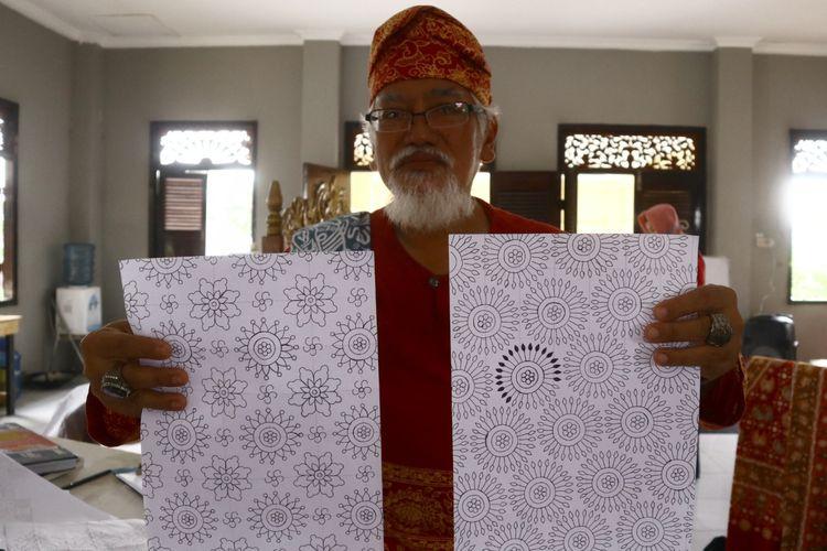 Zainul Bahri saat menunjukkan gambar pola batik corona yang dibikinnya di rumah tenun yang dikelolanya.