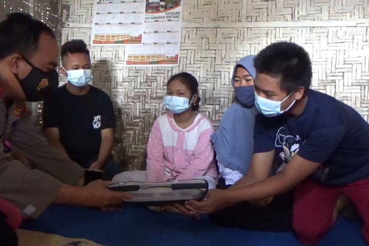 Aldi (15) siswa tidak mampu saat menerima bantuan dari Kapolsek Tanjung Seneng, Ipda Rosali. Aldi dan kakaknya, Adit sering bergantian mengenakan pakaian bagus saat menerima tamu.