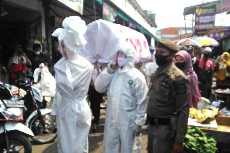 Boneka pocong dan keranda mayat diarak keliling pasar tradisional Kecamatan Cikupa untuk membuat warga mau mengenakan masker, Senin (31/8/2020)