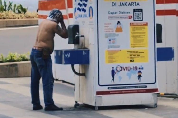 Seorang pria keramas di tempat cuci tangan tepatnya di dekat Gedung Indofood Tower di Jalan Jenderal Sudirman, Setiabudi, Jakarta Selatan pada Jumat (9/4/2021) pukul 11.30 WIB.