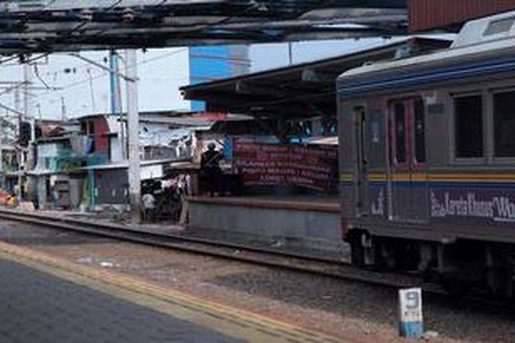 KRL Comuter Line berhenti di Stasiun Kampung Bandan, Jakarta Utara, untuk menaik turunkan penumpang, Jumat (10/5/2013). Stasiun ini berada di antara pusat perbelanjaan dan pemukiman kumuh warga.