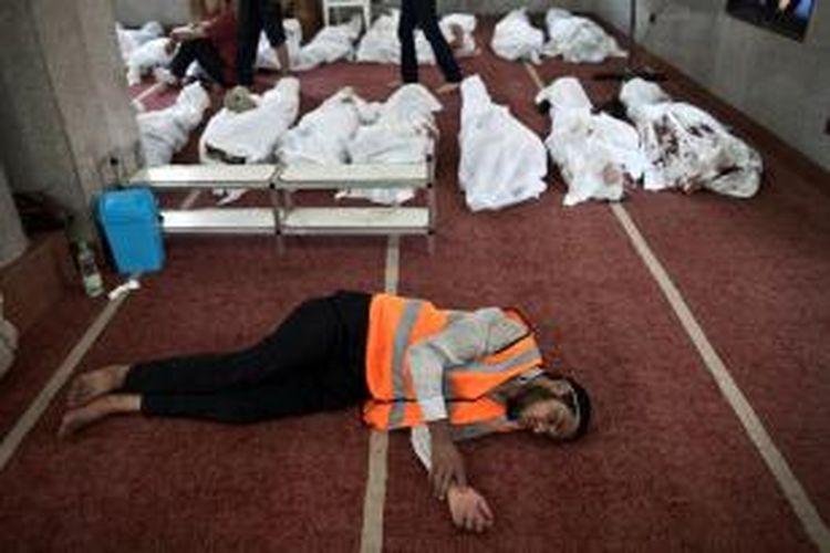 Seorang sukarelawan tertidur karena kelelahan sementara di belakangnya puluhan jenazah korban kerusuhan disemayamkan di sebuah masjid di kota Kairo, Mesir. Bentrokan antara aparat keamanan dan pengunjuk rasa pro-Mursi telah menewaskan 525 orang.