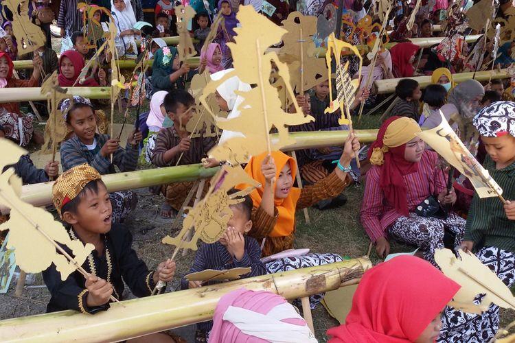 Ratusan anak ikut menarikan wayang kertas ketika menyaksikan dalang cilik Kevin Rabbani beraksi di panggung wayang di Balai Desa Tayuban, Panjatan, Kulon Progo, DI Yogyakarta. Wayang kertas di tangan anak-anak itu jadi seperti mainan yang menyenangkan mereka.
