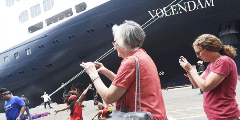 Wisatawan memotret kelompok kesenian Gembong Kyai Bulak yang menyambut kedatangan Kapal Pesiar MS Volendam berbendera Belanda di Pelabuhan Tanjung Perak Surabaya, Jawa Timur, Senin (14/11/2016). Selain mendapat suguhan pentas kesenian, 1.400 penumpang akan mengunjungi sejumlah obyek wisata di Surabaya.