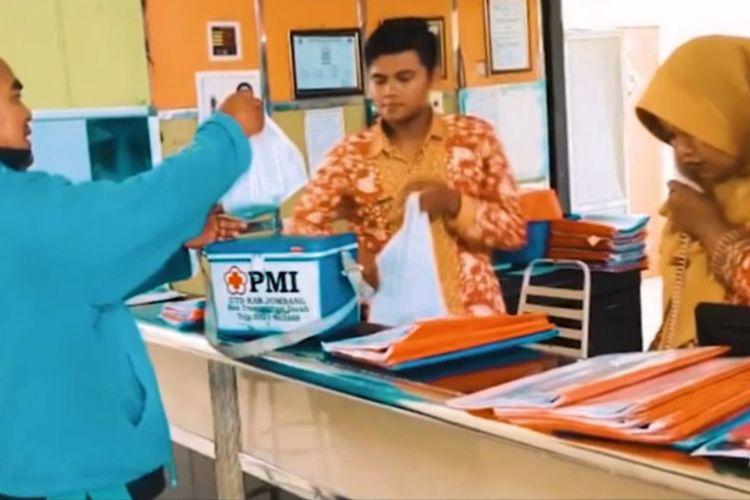 Salah seorang tukang ojek yang turut berpartisipasi, saat menyerahkan pesanan darah kepada perawat di RSUD Ngimbang.