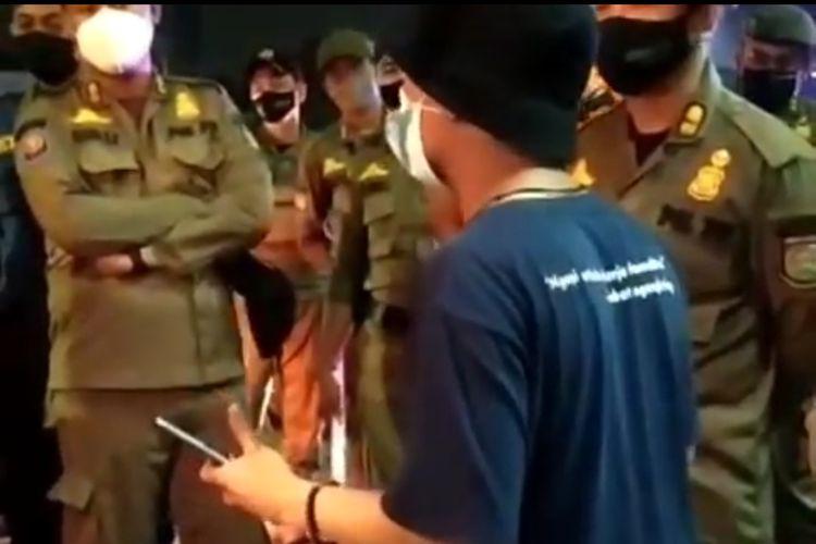 Shofwan, pemilik lapak di Pamulang, Tangerang Selatan, saat memberi penjelasan ke beberapa personel gabungan yang tengah menertibkan lapaknya, Minggu (18/7/2021).