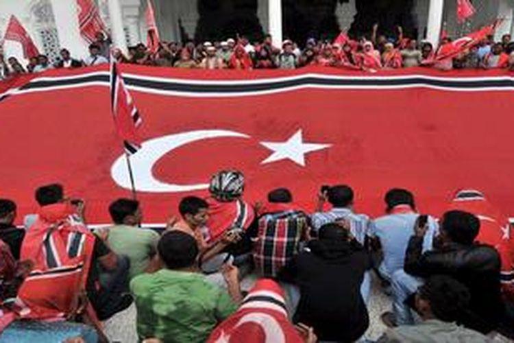 Warga pendukung Qanun Bendera dan Lambang Aceh membentangkan bendera berukuran jumbo, yakni 13,4 meter x 6,4 meter di halaman Masjid Raya Baiturrahman, Banda Aceh, Aceh, Senin (1/4/2013). Mereka mendesak Pemerintah Pusat untuk tidak merevisi Qanun Bendera dan Lambang Aceh.