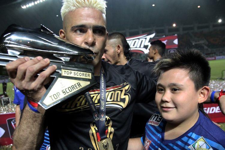 Striker Arema FC, Cristian Gonzales, memamerkan sepatu emas tanda penghargaan pencetak gol terbanyak Piala Presiden 2017 seusai laga final di Stadion Pakansari, Minggu (12/3/2017).