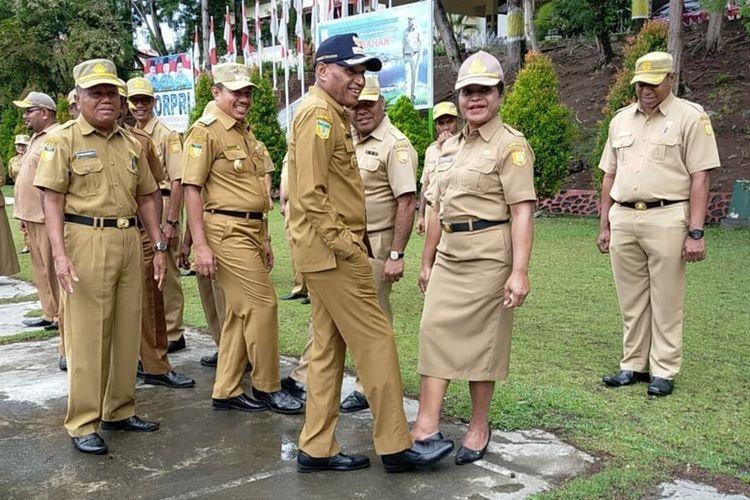 Wali Kota Jayapura Benhur Tommy Mano (topi hitam) bersalaman menggunakan kaki dengan salah satu ASN, Jayapura, Papua, Senin (16/3/2020).