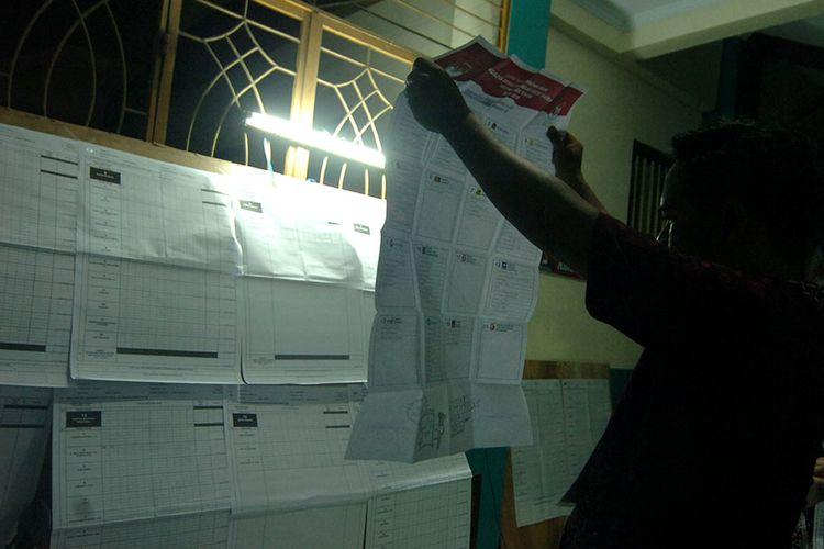 Anggota KPPS melakukan penghitungan surat suara di TPS 09 Kelurahan Mangkukusuman, Tegal, Jawa Tengah, Rabu (17/4/2019) malam.