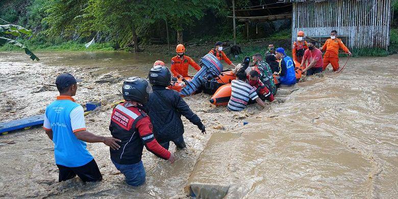 Petugas BPBD, Tagana, TNI dan Polri bersama masyarakat  mengevakuasi korban banjir dengan menggunakan perahu karet di Desa Alale, Kabupaten Bone Bolango, Gorontalo, Kamis (11/6/2020). Petugas gabungan terus berusaha mengevakuasi warga yang masih terjebak dalam rumah mereka.