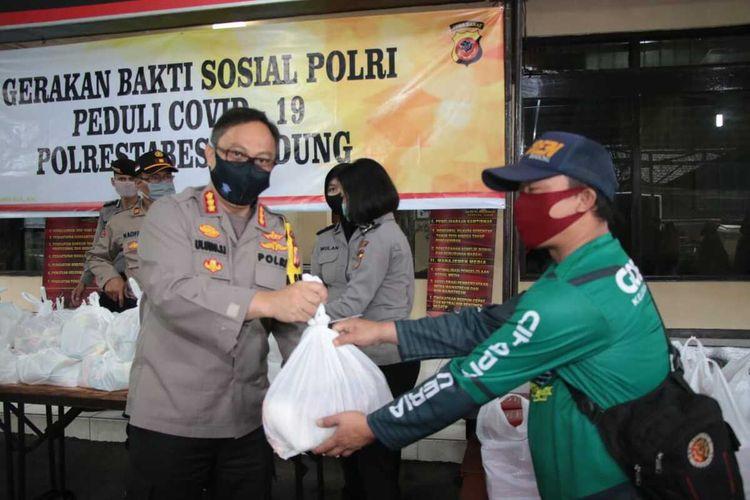 Kapolrestabes Bandung Kombes Pol Ulung Sampurna Jaya tengah membagikan sembako kepada salah satu warga kota Bandung.
