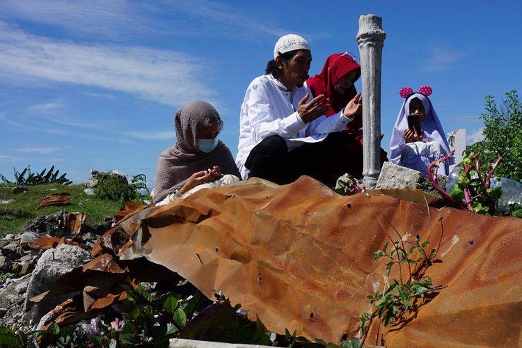 Warga berdoa di tempat hilangnya anggota keluarga mereka di lokasi bekas terdampak likuefaksi di Kelurahan Balaroa, Palu, Sulawesi Tengah, Rabu (5/6/2019). Usai melaksanakan shalat Idul Fitri, umat muslim korban bencana mendatangi lokasi permukiman penduduk yang hancur akibat gempa dan likuefaksi tersebut untuk mengenang dan mendoakan keluarga mereka yang meninggal dunia atau dinyatakan hilang dalam peristiwa tersebut. ANTARA FOTO/Mohamad Hamzah/hp.