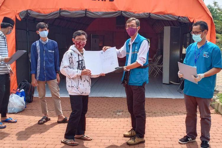 Koordinator Bidang Penanganan Satuan Gugus Tugas Covid-19 Tangerang Selatan Suhara Manullang bersama salah seorang Santri yang diperbolehkan pulang dari Rumah Lawan Covid-19 Kota Tangerang Selatan, Kamis (30/7/2020)