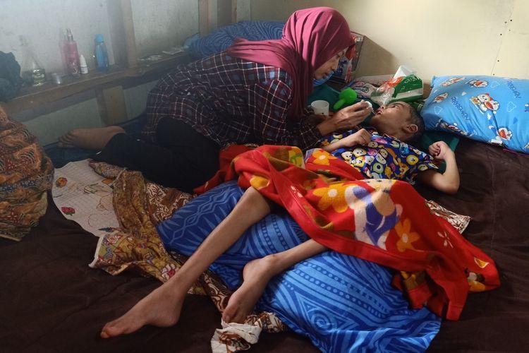Alit Rokayah (45) tengah memberikan air minum kepada anak angkatnya Rizki (7). Rizki diduga menjadi korban kekerasan yang dilakukan orangtua kandungnya.